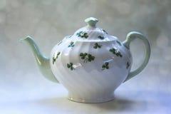 Irische Tee-Topf-Shamrocks mit Bokeh-Hintergrund Lizenzfreie Stockfotos