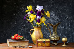 Irises in a ceramic vase and fresh strawberries. On table Royalty Free Stock Images
