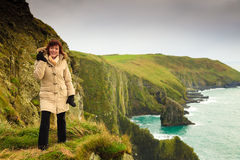 Irish atlantic coast. Woman tourist standing on rock cliff Royalty Free Stock Photos