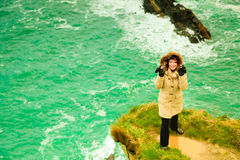 Irish atlantic coast. Woman tourist standing on rock cliff. By the ocean Co. Cork Ireland Europe. Beautiful sea landscape beauty in nature Royalty Free Stock Photography