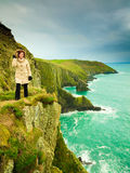 Irish atlantic coast. Woman tourist standing on rock cliff Royalty Free Stock Photo