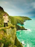 Irish atlantic coast. Woman tourist standing on rock cliff. By the ocean Co. Cork Ireland Europe. Beautiful sea landscape beauty in nature Royalty Free Stock Photo