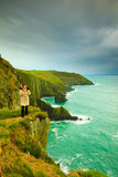 Irish atlantic coast. Woman tourist standing on rock cliff. By the ocean Co. Cork Ireland Europe. Beautiful sea landscape beauty in nature Stock Images