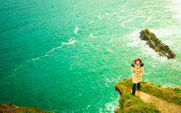 Irish atlantic coast. Woman tourist standing on rock cliff Royalty Free Stock Photography