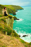 Irish atlantic coast. Woman tourist standing on rock cliff Royalty Free Stock Image
