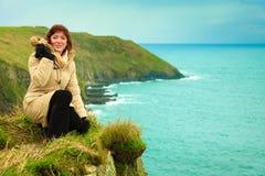 Irish atlantic coast. Woman tourist standing on rock cliff. By the ocean Co. Cork Ireland Europe. Beautiful sea landscape beauty in nature Stock Image