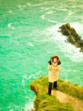 Irish atlantic coast. Woman tourist standing on rock cliff Stock Image