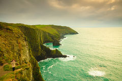 Irish atlantic coast. Woman tourist standing on rock cliff Royalty Free Stock Images