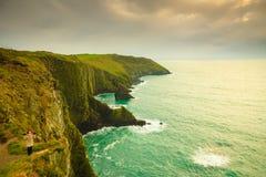 Irish atlantic coast. Woman tourist standing on rock cliff Royalty Free Stock Images