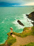 Irish atlantic coast. Woman tourist standing on rock cliff Royalty Free Stock Photo