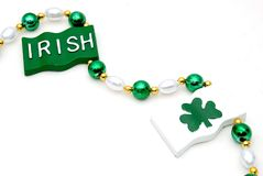 Irish beaded necklace. A beaded necklace with green, gold, and white beads and the word irish and aclover on a flag shaped sign vector illustration