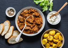 Irish beef stew and turmeric potatoes - delicious seasonal lunch on a dark background, top view. Flat lay. Comfort food royalty free stock image