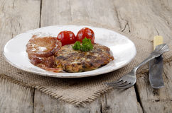 Irish boxty on a plate. Warm irish black pudding boxty with grilled bacon and cherry tomato on a plate Royalty Free Stock Photo
