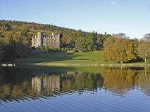 Irish castle by a lake. Castlewellan castle, Ireland, reflecting onto the lake in the evening sun Stock Photo