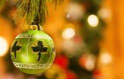 Irish Christmas with lucky shamrock. Celebrating Christmas at the Irish with lucky shamrock and green bauble. Over defocused lights Stock Photos