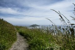 An Irish cliff walk above the ocean. With an island in the background stock photo