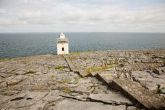 Irish coastline, sea and horizon, broken rock ground with light house. Sea shore, flat, cracked stone surface with steps leading to a white light house Stock Photo