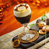Irish coffee cocktail and biscuits with shadows. An irish coffee cocktail made with coffee and some cream on top in a transparent long glass sitting on a small Royalty Free Stock Image