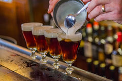 Irish Coffee at the famous Buena Vista cafe in San Francisco. San Francisco, USA - May 2, 2014: Irish Coffee drinks being made on the bar counter at the famous Stock Photography