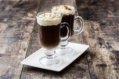 Irish coffee in glas op hout stock afbeeldingen