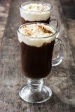 Irish coffee in vetro su legno fotografia stock