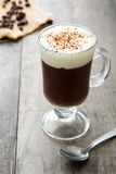 Irish coffee in vetro su legno fotografia stock