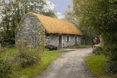 Irish cottage. A thached roofed irish cottage made of stone with a path passsing by with a grass lawn and trees Stock Photography