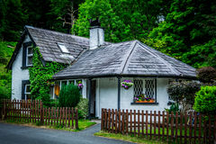 Irish cottage. The entrance of the Powerscourt waterfall in Wicklow county, Republic of Ireland. Cute white irish cottage with green background of trees and Stock Images