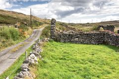 Irish Country Road by Church Ruins. Remote road leading past the ruins of an old church near the Healy Pass, Beara Peninsula, West Cork, Ireland stock image