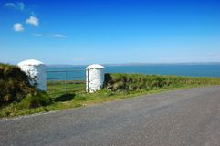 Irish country road in kerry. White Pillars & Gate overlooking ocean near Ballybunion, Co. Kerry, Ireland Stock Photography