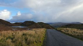 Irish country road and a small lake. Road in the countryside and small lake royalty free stock image