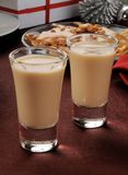 Irish cream shooters. Two Irish Cream shooters in shot glasses on a table with Christmas gifts and decorations Stock Photography
