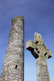 Irish Cross in front of tower. Irish Cross in front of a Monastic round tower and blue sky royalty free stock images