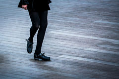 Irish Dancer with a Black Dress. Legs and feet of a female Irish dancer using the traditional Irish dancing hardshoes on parquet royalty free stock photography