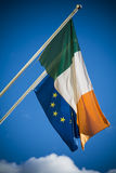 Irish and European Union flags together against blue sky royalty free stock photography