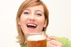 Irish eyes. Smiling woman drinking a big glass beer Royalty Free Stock Photos