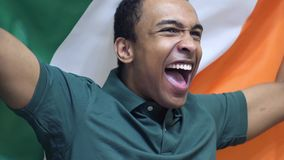 Irish Fan Celebrating while holding the Flag of Ireland in Slow Motion. High quality royalty free stock photos