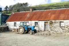 Irish Farm Longhouse and tractor in Wicklow. Irish Farm Longhouse with traditional corrugated iron roof and tractor in the Wicklow Mountains on the east coast of stock photography