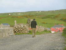 Irish farm worker. End of a working day. Irish farm worker walking wearily along a track. With an Irish landscape in the background, and a traditionally painted Stock Photography