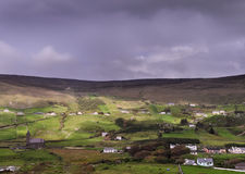 Irish farming countryside with traditional houses on hillside Stock Photography