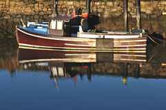Irish Fishing Boat and its Reflection. At the dock in Belfast, Northern Ireland Stock Photo