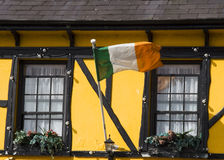 Irish flag. Flying outside a painted yellow house stock images