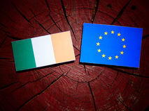 Irish flag with EU flag on a tree stump isolated. Irish flag with EU flag on a tree stump Royalty Free Stock Photo