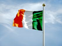 Irish flag fluttering in a bright blue sky. Irish flag fluttering in a brisk breeze against a bright blue sky. The national flag of Ireland frequently referred royalty free stock photos