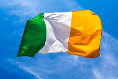 Irish flag fluttering in a brisk breeze against a bright blue sk. Y. Europe stock photos