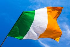 Irish flag fluttering in a brisk breeze against a bright blue sk. Y. Europe royalty free stock images