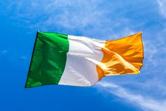 Irish flag fluttering in a brisk breeze against a bright blue sk. Y. Europe stock photo