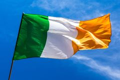 Irish flag fluttering in a brisk breeze against a bright blue sk. Y. Europe royalty free stock image
