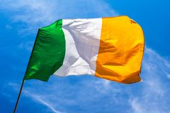 Irish flag fluttering in a brisk breeze against a bright blue sk. Y. Europe royalty free stock photography
