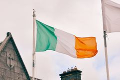 Irish flag waving on wind. Irish flag fluttering waving in the wind. Patriotic national landmarks of Ireland stock photo